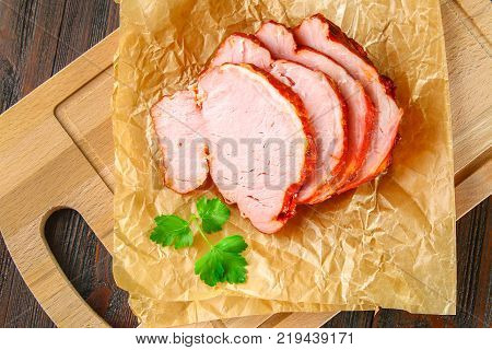 Sliced Roast Pork Loin on a brown wooden table with cilantro