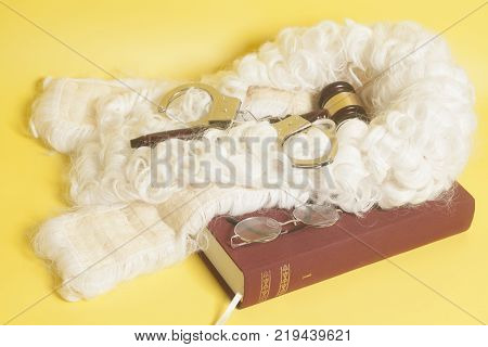set for judge:judge wig, handcuffs,judge gavel, book end eyeglasses on yellow background