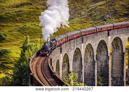 GLENFINNAN, SCOTLAND, UNITED KINGDOM - SEPTEMBER 9, 2015 : Glenfinnan Railway Viaduct in Scotland with the Jacobite steam train passing over