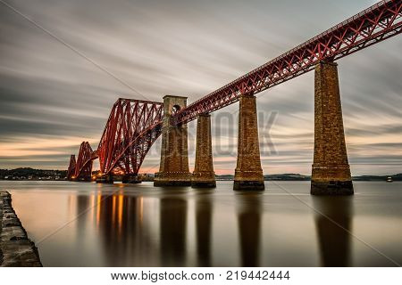 Forth Railway Bridge over the Firth of Forth at sunset in Edinburgh, Scotland, United Kingdom. Long exposure.