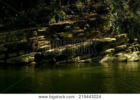 A picturesque small cliff above a river whirlpool in a rainforest