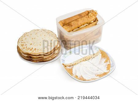 Thin round pancake on a dish during rolling up with cottage cheese filling stack of not rolled pancakes and rolled up pancakes in plastic container on a white background