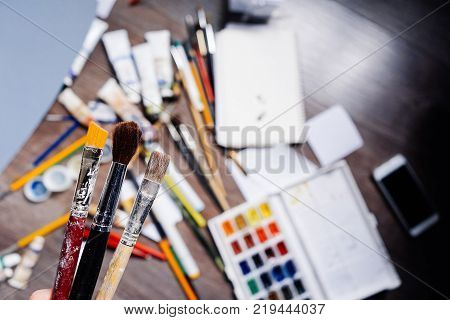 on the wooden floor are many art brushes, watercolors and gouache