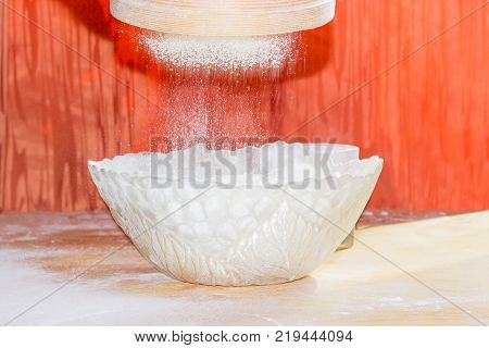Wheat flour during sifting through a wooden sieve into a glass bowl