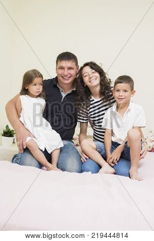 Family Ideas. Happy caucasian Family of Two Parent and Two Kids Sitting Together Embraced.Vertical Image Composition