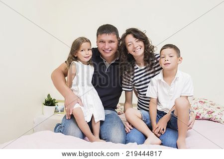 Family Ideas. Happy caucasian Family of Two Parent and Two Kids Sitting Together Embraced and Smiling Happily. Horizontal Image Composition
