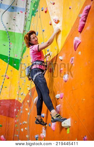 A white middle aged woman trains on a climbing wall with smile on her face.