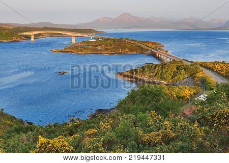 Skye from Kyle of Lochalsh, in the mainland Highlands of Scotland, in a sunny, bright day. Despite the boats and ferries docked at the loch harbor, the main link for transportation is the long bridge