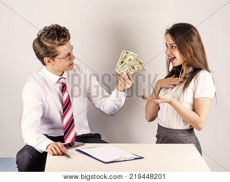 The concept of gratitude. A young handsome man gives money to a beautiful freelancer. Gray background.