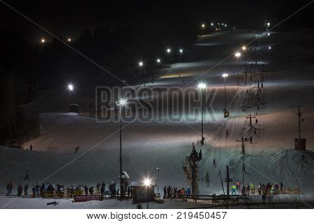 5 January 2017. Zuberec Ski Park. Slovakia. Western Tatras. Europe. Ski with the lift at night lit by lanterns. Night skiing. Adults and children skiing after work. Concept of healthy active lifestyle.