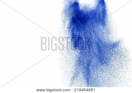 Blue colored sand explosion isolated on white background. Abstract sand cloud. Blue colored sand splash agianst on clear background. Sandy fly wave in the air.