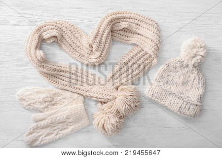 Warm knitted clothes on wooden background. Seasonal female wardrobe
