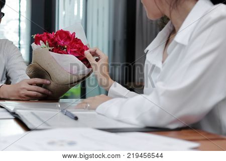 Vintage toned image of attractive young Asian woman accepting a bouquet of red roses from boyfriend in office on valentine's day. Love and romance in workplace concept.