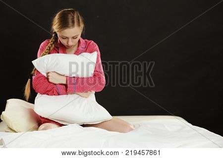 Adolescence problems concept. Sad young teenager woman sitting on bed feeling depressed hugging pillow.