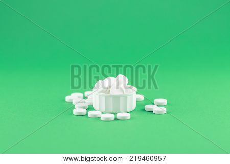 Close Up White Pill Bottle On Jade Green Background With Copy Space. Focus On Foreground, Soft Bokeh
