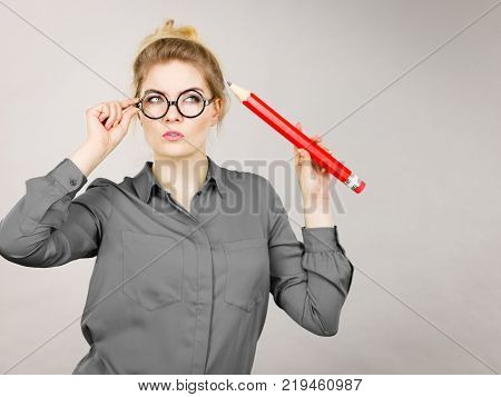 Person confused thinking seeks a solution. Pensive thoughtful student girl or business woman female teacher coming up with an idea holding big red pencil. Studio shot on grey.