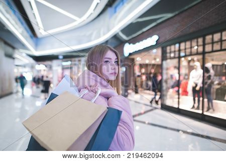 A sweet blonde with shopping bags in the yoke goes to the mall and looks to the side. Shopping concept