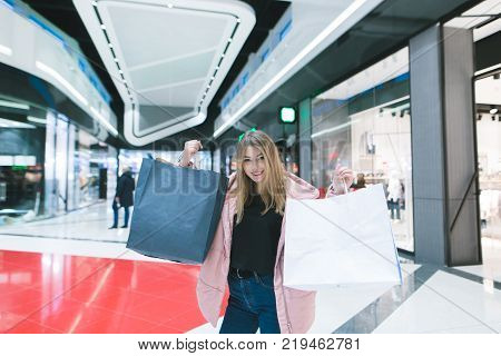 Beautiful girl rejoices in shopping. Portrait of a girl with shopping bags in the background of shopping mall. Shopping concept