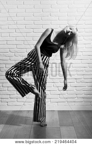 Black and white full length monochrome portrait of an attractive young woman posing artistically at studio balance dacing beauty weightless modelling concept.