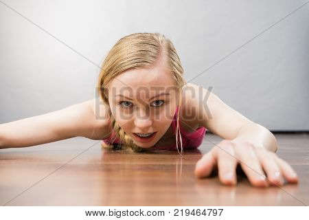 Young woman lying on floor face closeup she pretending like something is pulling her back.