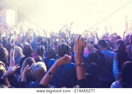 A crowd of spectators at a concert in a small concert club. Applaud and dance near the stage. The audience is filled with light.
