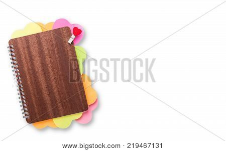 Book of love wooden cover notebook with multi-colored heart shaped posted it and cloth pin on white background with room for text valentine or love theme concept