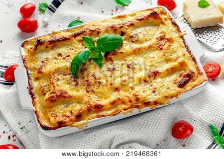 Homemade lasagna with minced beef bolognese and bechamel sauce topped wild basil, parmesan cheese.