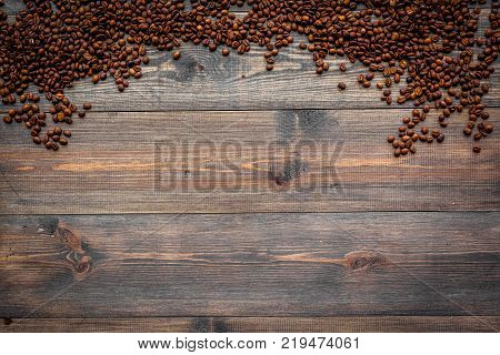Scattered coffee beans on dark wooden table top view copyspace. Coffee background