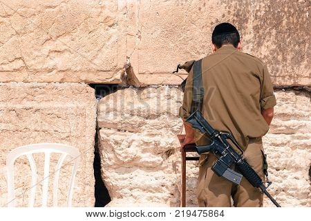 Horizontal picture of the back of Israeli man soldier praying at The Western Wall the Kotel at Jewish Quarter inside the walls of Old City in Jerusalem Israel
