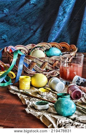 Easter. Eggs in a basket and colored paints on a wooden table.Image of the process of coloring Easter eggs at home.
