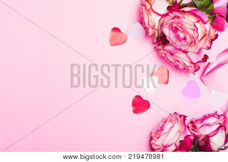 Beautiful pink rose, decorative confetti hearts and pink ribbon on pink Valentines day background. Copy space
