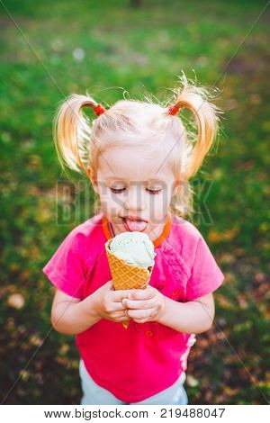 little funny Caucasian girl blonde with blue eyes with two tails on head eating an ice cream in a waffle cup of blue sitting on green grass.All face dirty in melted ice cream.Looks down at the camera.