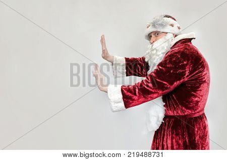 Santa Claus pushes copy space with his hands isolated on gray background.
