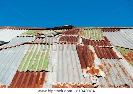 Rusted old corrugated iron roof against clear blue sky