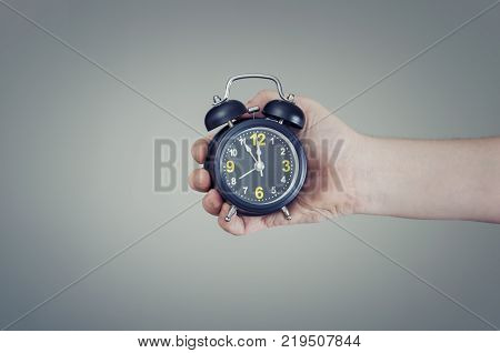 Time for decisions. Alarm clock in hand showing five to twelve.