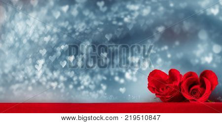 Two heart shaped red roses on fabric over glitter background, Valentines day