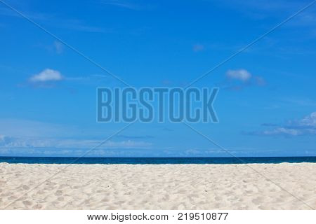 White sandy tropical beach and sea under blue clear sky