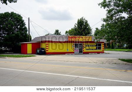 JOLIET, ILLINOIS / UNITED STATES - JULY 26, 2017: The red and yellow cinder block building, which previously housed Moody's Fish and Chicken restaurant, is for sale or lease.