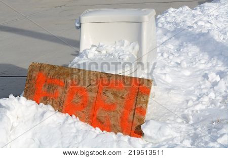 White porcelain toilet discarded on sidewalk in snow bank with a sign stating free to take
