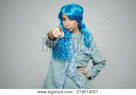 Dissatisfied offended and recentful girl pout her mouth with blue hair showing ahead with her index finger isolated on gray background.
