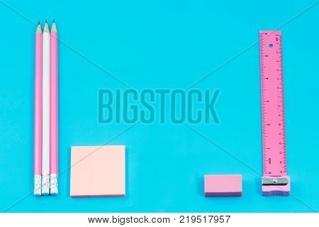 Stationary concept Flat Lay. Stationary about pencils paper note ruler rubber and Pencil sharpener pastel tone on blue background with copy space.