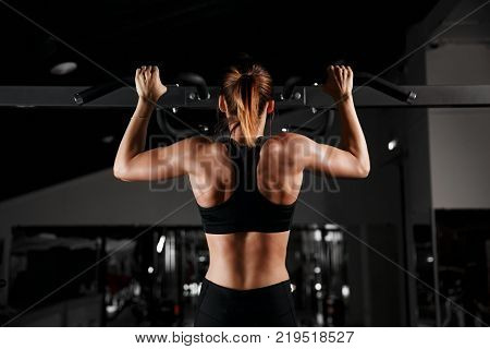 Strong fit girl in sportswear doing pull up exercise on horizontal bar. Fitness workout in gym. Muscular young woman.