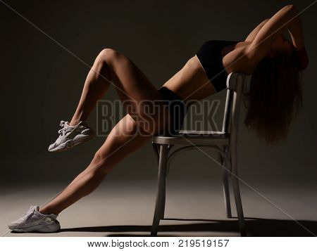 Silhouette Of A Beautiful Sports Girl Sitting On The Edge Of A Chair Straight Legs