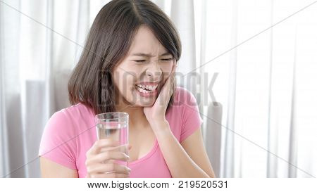 woman take water and feel bad with toothache in the home