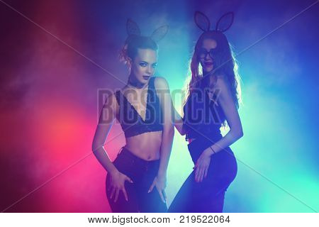 Disco, night party concept. Two attractive sexy girls dancing at a night party. Beauty, fashion. Entertainment.