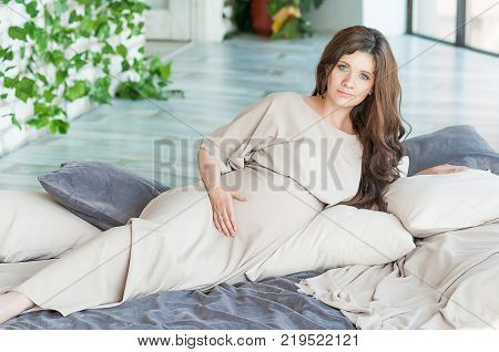 pregnant brunette woman lying on a bed looks at the camera, her hand lies on the belly