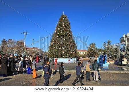 ASHGABAT TURKMENISTAN - January 04 2017: New Year tree in the square near the circus. People with children are walking near the decorated Christmas tree.