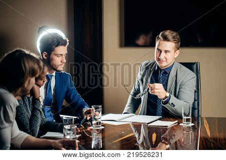 team leader and business owner leading informal in-house business meeting in office