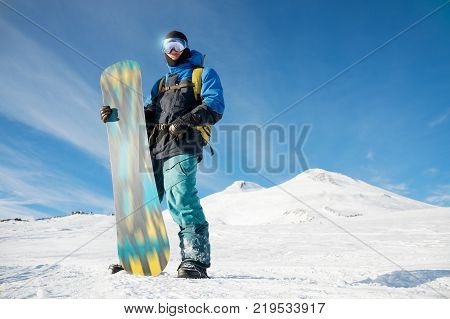 A professional snowboarder stands with his snowboard against the backdrop of the sleeping Elbrus volcano. North Caucasus. Procurement for advertising or poster with copy space. concept of winter sports and recreation