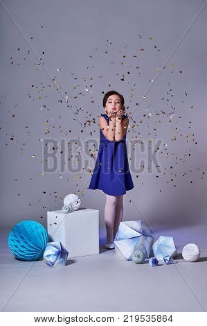 Beautiful happy brunette girl kid smiling and confetti falls everywhere. Time for a party. Pretty girl in an elegant blue dress for teenage girls with a make-up. New Year's party. Christmas Eve. Minimalism and origami
